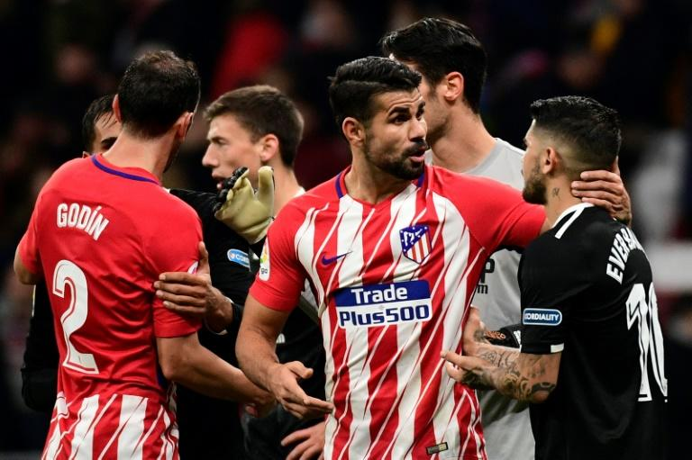 Atletico Madrid's Diego Costa (C) talks to Sevilla's Ever Banega at the end of their Spanish Copa del Rey match, at the Wanda Metropolitano stadium in Madrid, on January 17, 2018