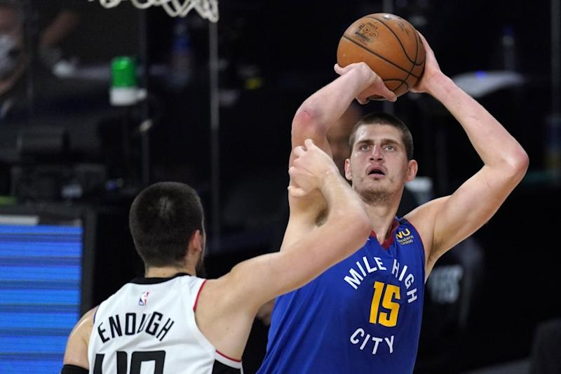 Denver Nuggets' Nikola Jokic, right, goes up for a shot against Los Angeles Clippers' Ivica Zubac during the first half of an NBA conference semifinal playoff basketball game, Friday, Sept. 11, 2020, in Lake Buena Vista, Fla. (AP Photo/Mark J. Terrill)