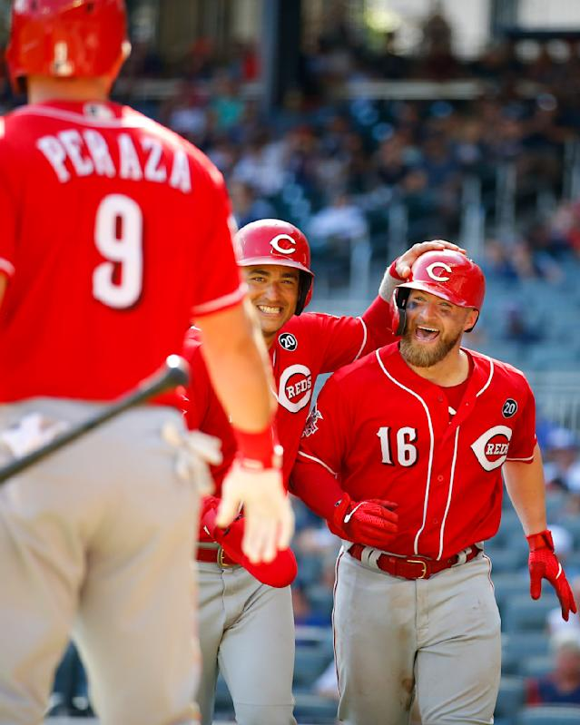Cincinnati Reds' Tucker Barnhart (16) reacts with Jose Iglesias and Jose Peraza after hitting a three-run home run in the tenth inning of a baseball game against the Atlanta Braves, Sunday, Aug.4, 2019, in Atlanta. (AP Photo/Todd Kirkland)