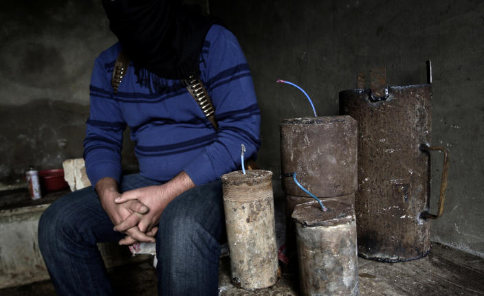 In this Friday, Dec. 14, 2012, Syrian rebel bomb maker Abu Moawiya sits next to bombs as he waits for other rebels to transfer them to another location, at their post in Maaret Misreen, near Idlib, Syria. The new Syrian rebel chief, a defected army general who spent months in exile, says he has begun operating inside Syria to unite autonomous anti-regime militias for what he hopes will be the final push against President Bashar Assad. (AP Photo/Muhammed Muheisen)