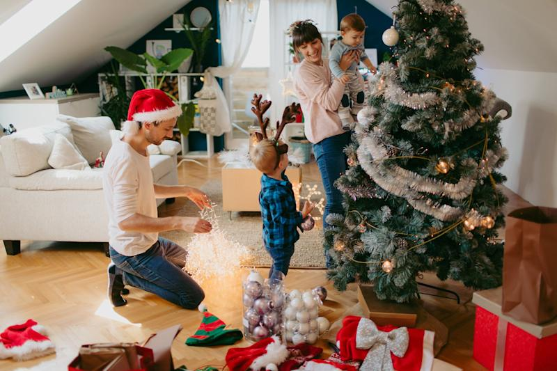 Photo of a cute little family with two children, decorating Christmas tree.