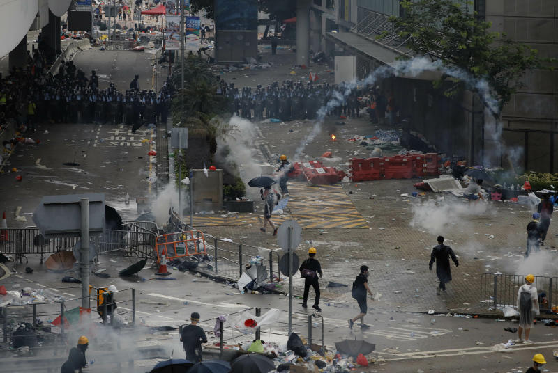 Riot police fire tear gas towards protesters outside the Legislative Council in Hong Kong, Wednesday, June 12, 2019. Hong Kong police have used tear gas and high-pressure hoses against thousands of protesters opposing a highly controversial extradition bill outside government headquarters. (AP Photo/Vincent Yu)