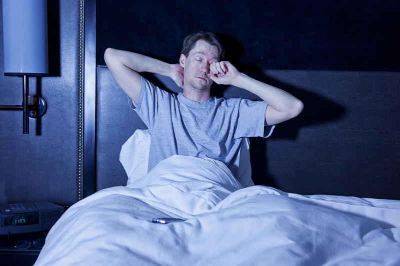 Photo of a man sitting in a hotel room bed bed, rubbing his tired eyes as he watches late night television with the remote control in his lap.