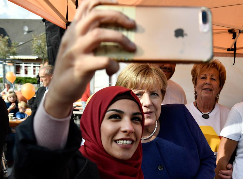 A Syrian refugee poses for a selfie with Angela Merkel during a campaign stop a week before the election.