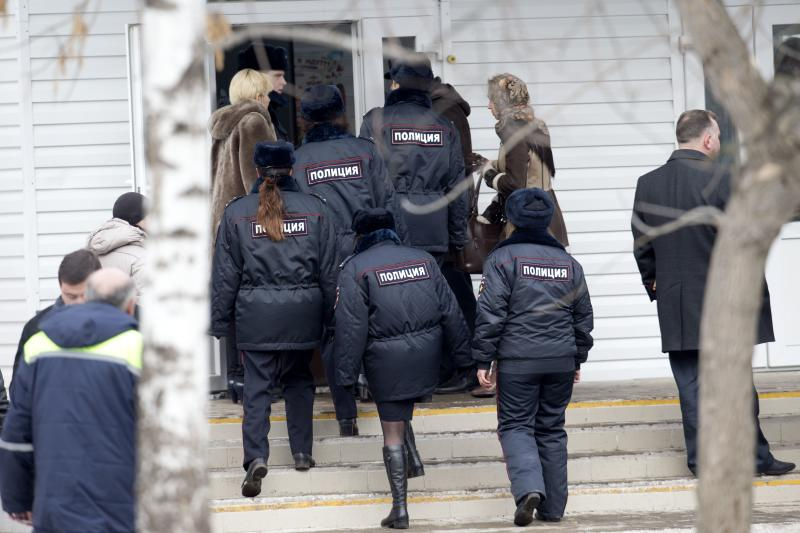 Police officers enter a Moscow school with a teacher on Monday, Feb. 3, 2014. An armed teenager burst into his Moscow school on Monday and killed a teacher and policeman before being taken into custody, investigators said. None of the children who were in School No. 263 were hurt, said Karina Sabitova, a police spokeswoman at the scene. The student also wounded a second police officer who had responded to an alarm from the school, she said. (AP Photo/Alexander Zemlianichenko)
