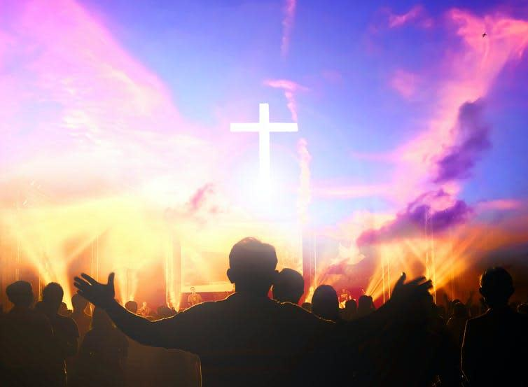 Colourful Christian chruch service with man holding arms out in prayer