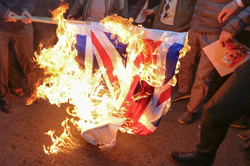 "Iranian demonstrators set alight a Union Jack in front of the British embassy in Iran's capital Tehran on January 12, 2020 following the British ambassador's arrest for allegedly attending an illegal demonstration. - Chanting ""Death to Britain"", up to 200 protesters rallied outside the mission a day after the brief arrest of British ambassador Rob Macaire at a memorial for those killed when a Ukraine airliner was shot down. (Photo by ATTA KENARE / AFP) (Photo by ATTA KENARE/AFP via Getty Images)"