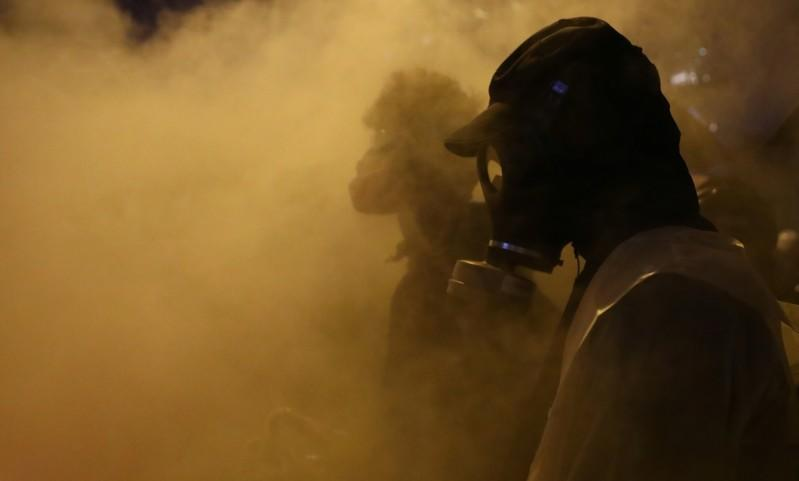 Anti-government protesters stand amid smoke during clashes with police, outside Hong Kong Polytechnic University