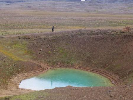 A woman walks past the smaller crater of the Krafla volcano near Reykjahlid, Iceland, September 19, 2015. Picture taken September 19, 2015. REUTERS/Lefteris Karagiannopoulos
