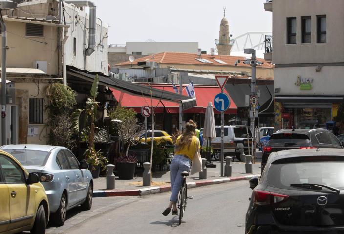 A woman rides a bicycle in the Jaffa neighborhood of Tel Aviv, Israel, Wednesday, April 21, 2021. Historic Jaffa's rapid gentrification in recent years is coming at the expense of its mostly Arab lower class. With housing prices out of reach, discontent over the city's rapid transformation into a bastion for Israel's ultra-wealthy is reaching a boiling point. (AP Photo/Sebastian Scheiner)