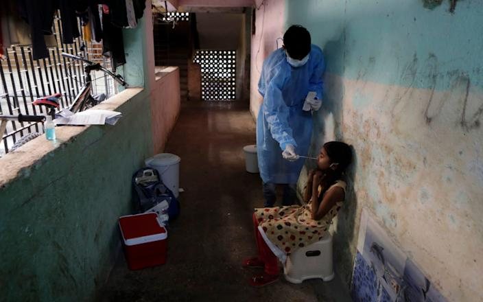 A health worker collects samples during a door-to-door screening campaign in Mumbai amid a surge of cases - Rajanash Kakade/AP
