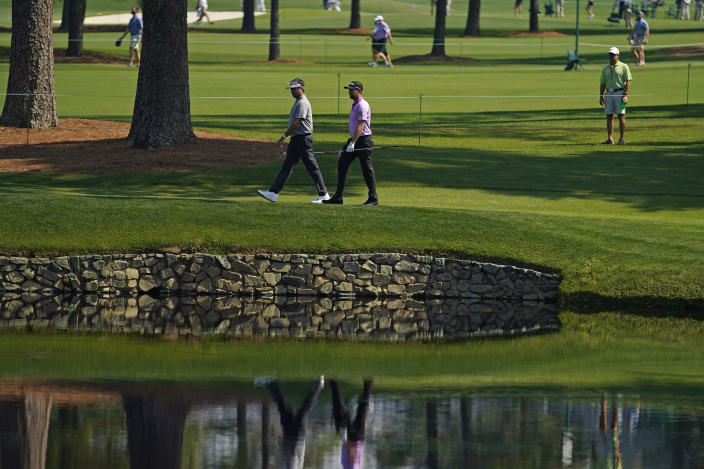 Bubba Watson, left, and Webb Simpson walk along the 15th fairway during a practice round for the Masters golf tournament on Wednesday, April 7, 2021, in Augusta, Ga. (AP Photo/Matt Slocum)
