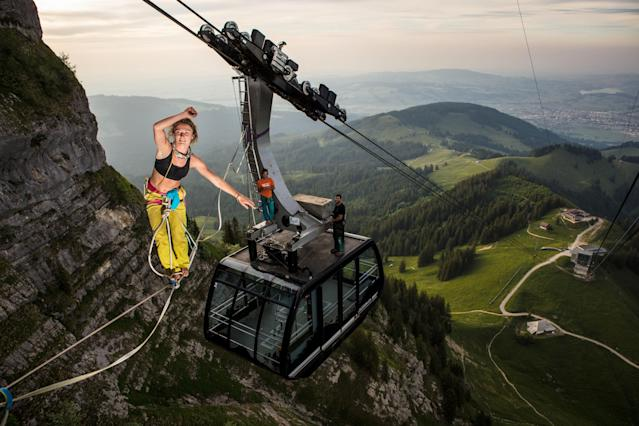 <p>Lenoble, 25, walks a slackline between two cable cars on the mountain of Moléson in Switzerland. (Photo: Martin Knobel/Caters News) </p>