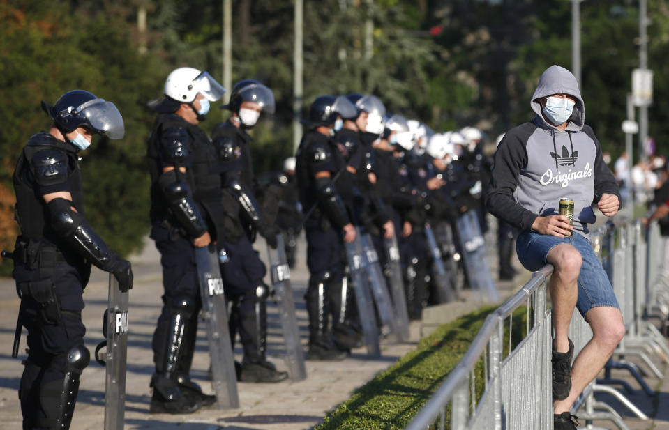 A man sits on a fence as the riot police guards the area in front of the Serbian Parliament building during a demonstration in Belgrade, Serbia, Wednesday, July 8, 2020. Serbia's president Aleksandar Vucic backtracked Wednesday on his plans to reinstate a coronavirus lockdown in Belgrade after thousands protested the move and violently clashed with the police in the capital. (AP Photo/Darko Vojinovic)
