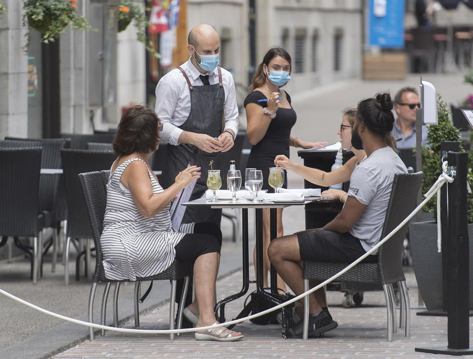Servers wear face masks as they take orders at an outdoor terrace in Montreal, Sunday, July 26, 2020, as the COVID-19 pandemic continues in Canada and around the world. (Graham Hughes/The Canadian Press via AP)