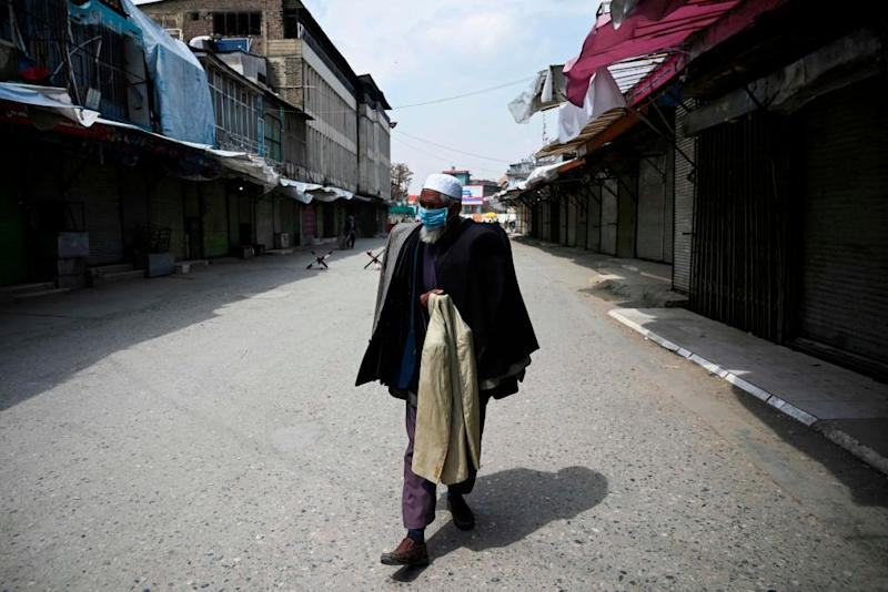 A man wears a face mask as he walks through a closed market in Kabul