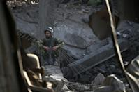 An Afghan National Army soldier sits inside a damaged building after a powerful truck bomb explosion in Kabul on August 7, 2015