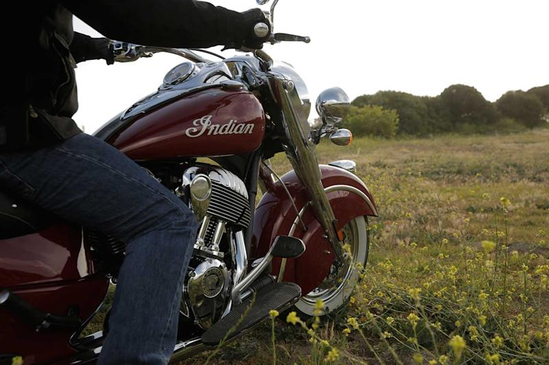 Man sitting in a meadow on his maroon Indian Motorcycle