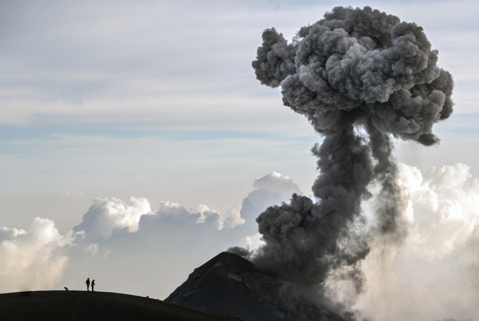 Hikers view Fuego Volcano as it erupts, from atop the Acatenango summit in Acatenango, Guatemala on Tuesday, March 16, 2021. (AP Photo/Josh Edelson)