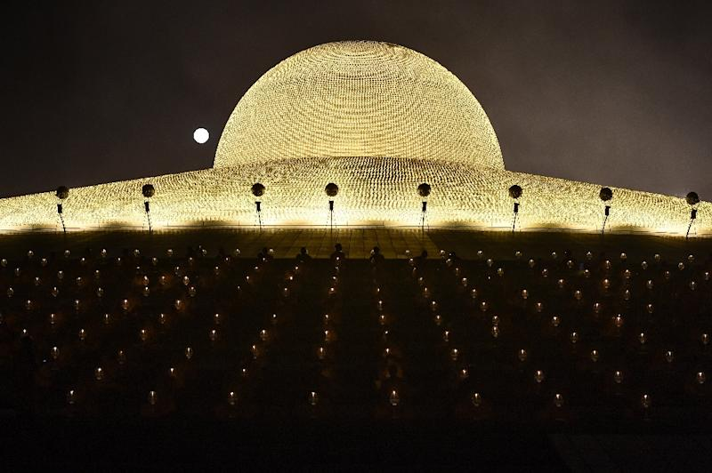 Buddhist monks pray with candles in front of a full moon to mark Makha Bucha Day at Wat Dhammakaya temple, just north of Bangkok, on February 11, 2017 (AFP Photo/LILLIAN SUWANRUMPHA)