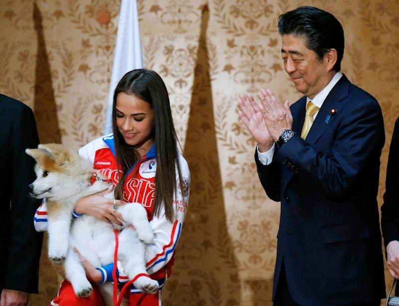Japanese Prime Minister Shinzo Abe helped present Russian figure skating gold medallist Alina Zagitova with an
