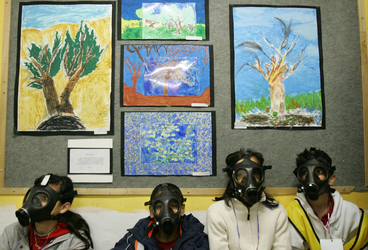 FILE - In this March 15, 2007 file photo Israeli school children wear gas masks during a drill organized by the Israeli Home Front Command simulating a chemical missile attack in a shelter at a school in the central Israeli city of Lod. Israel's outgoing civil defense chief said Wednesday, Aug. 15, 2012 that an attack on Iran's nuclear sites would likely trigger a drawn-out war that would last months and kill hundreds of Israelis.(AP Photo/Oded Balilty, File)