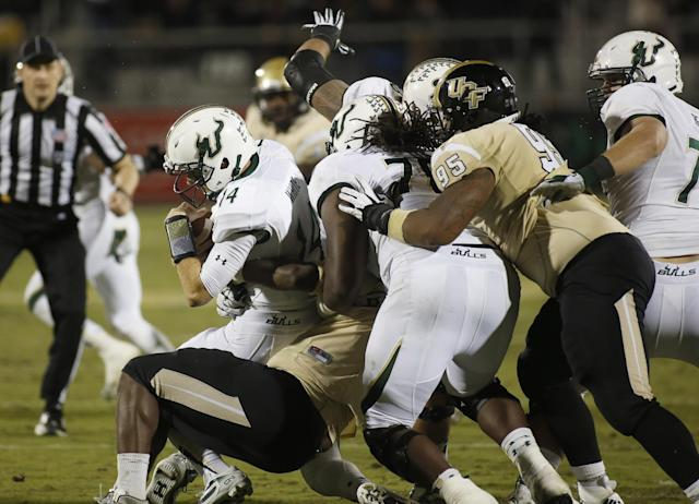 South Florida quarterback Mike White (14) is sacked by Central Florida defensive lineman Thomas Niles with help from defensive lineman E.J. Dunston (95) during the first half of an NCAA college football game on Friday, Nov. 29, 2013, in Orlando, Fla. (AP Photo/Reinhold Matay