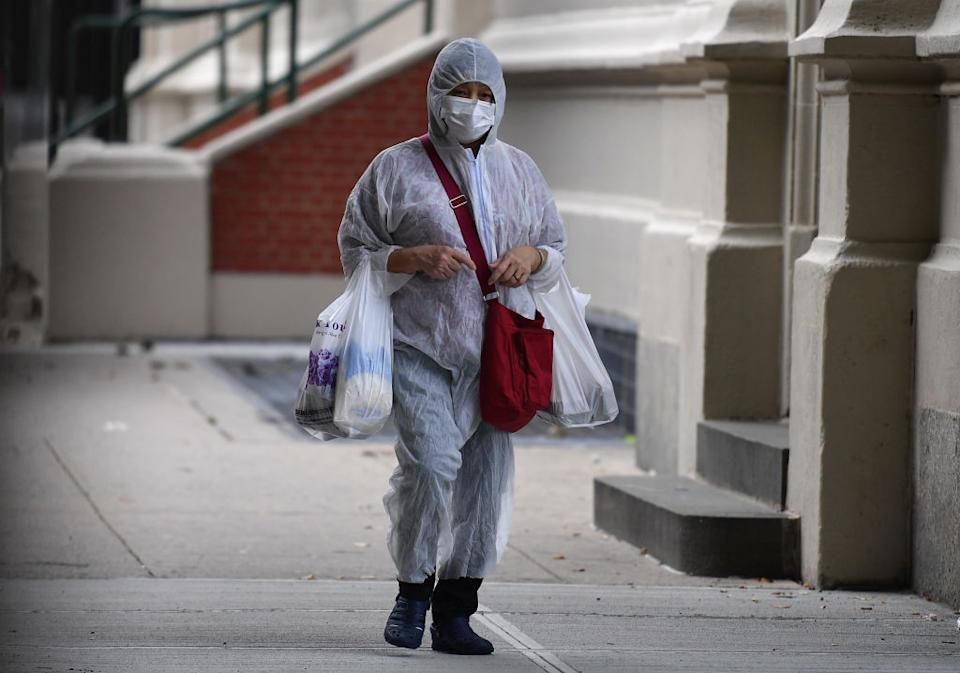 A person in a hazmat suit carries groceries in the street.