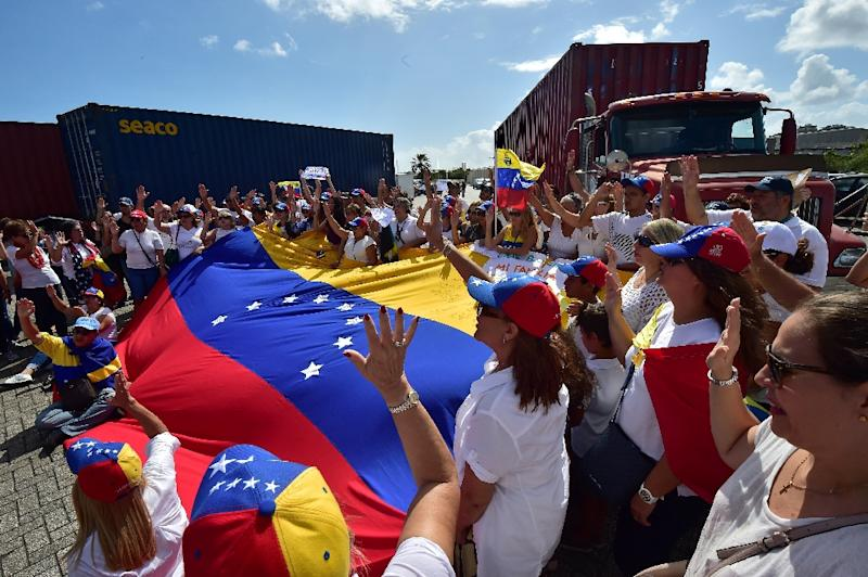 Flag-waving Venezuelan opposition supporters rallied on February 23, 2019 in the port of Willemstad, Curacao, where red trucks carried aid intended for Venezuela (AFP Photo/Luis ACOSTA            )