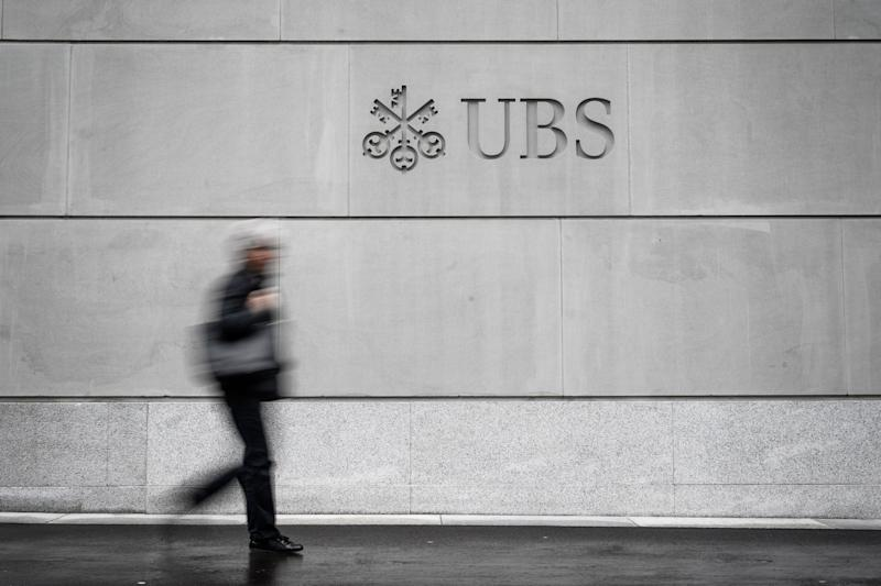 A pedestrian walks by the logo of Swiss banking giant UBS engraved on the wall of its headquarters on May 8, 2019 in Zurich. (Photo by Fabrice COFFRINI / AFP) (Photo credit should read FABRICE COFFRINI/AFP/Getty Images)