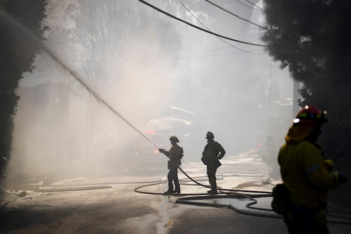 Los Angeles County Firefighters put out a house fire that was caused by the Getty Fire in the Brentwood Heights neighborhood of Los Angeles.