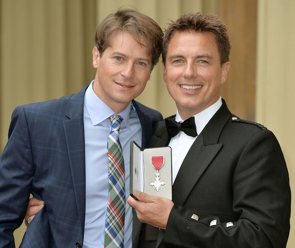 <p>Barrowman with his husband, Scott Gill, after being awarded an MBE at Buckingham Palace, October 2014</p>Getty