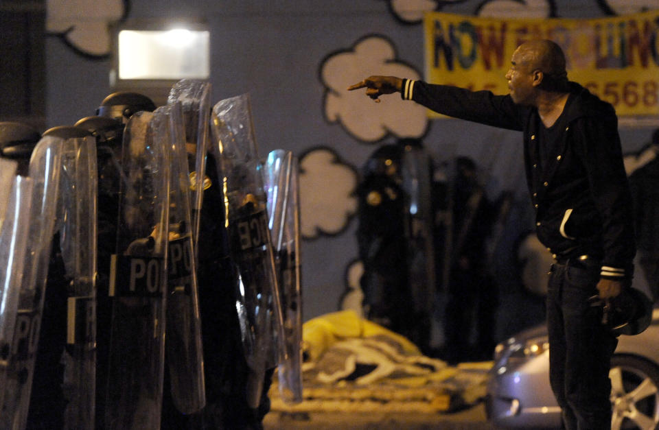 A protester points while facing police during a demonstration Tuesday night, Oct. 27, 2020, in Philadelphia. Hundreds of demonstrators marched in West Philadelphia over the death of Walter Wallace Jr., a Black man who was killed by police in Philadelphia on Monday. (AP Photo/Michael Perez)