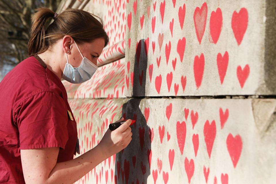 <p>A health worker draws a heart on the National Covid Memorial Wall on the Embankment</p> (PA)