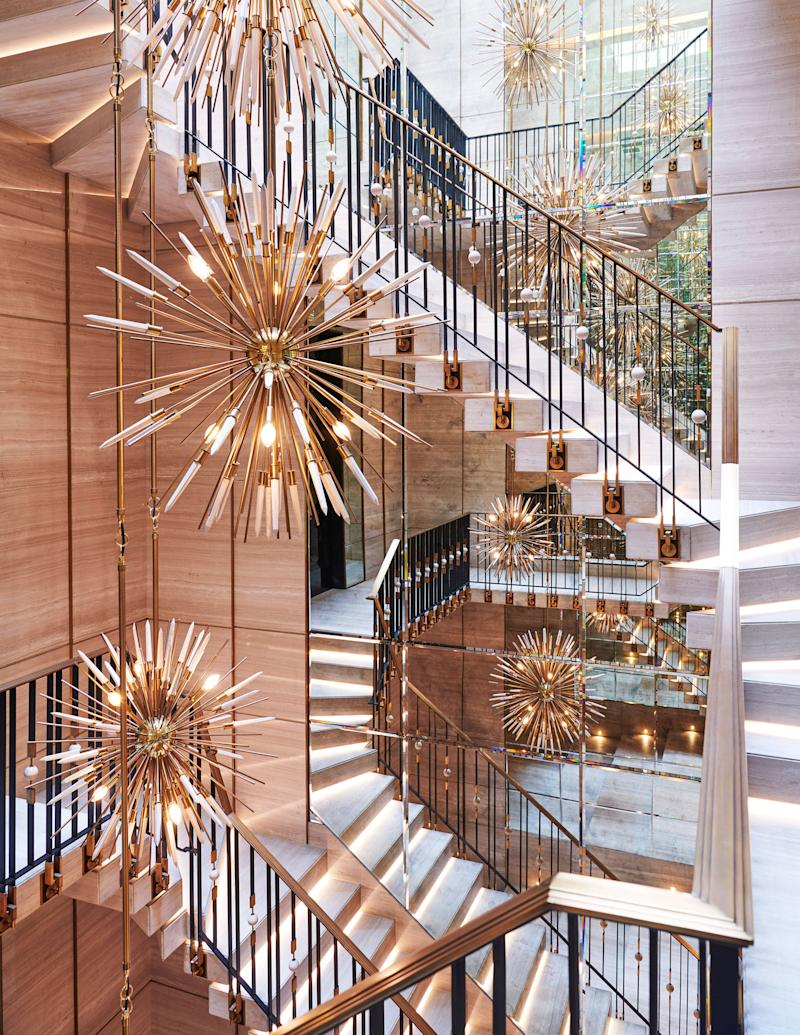 A suspended cantilevered block marble stair is adorned with chandeliers by Rafauli.