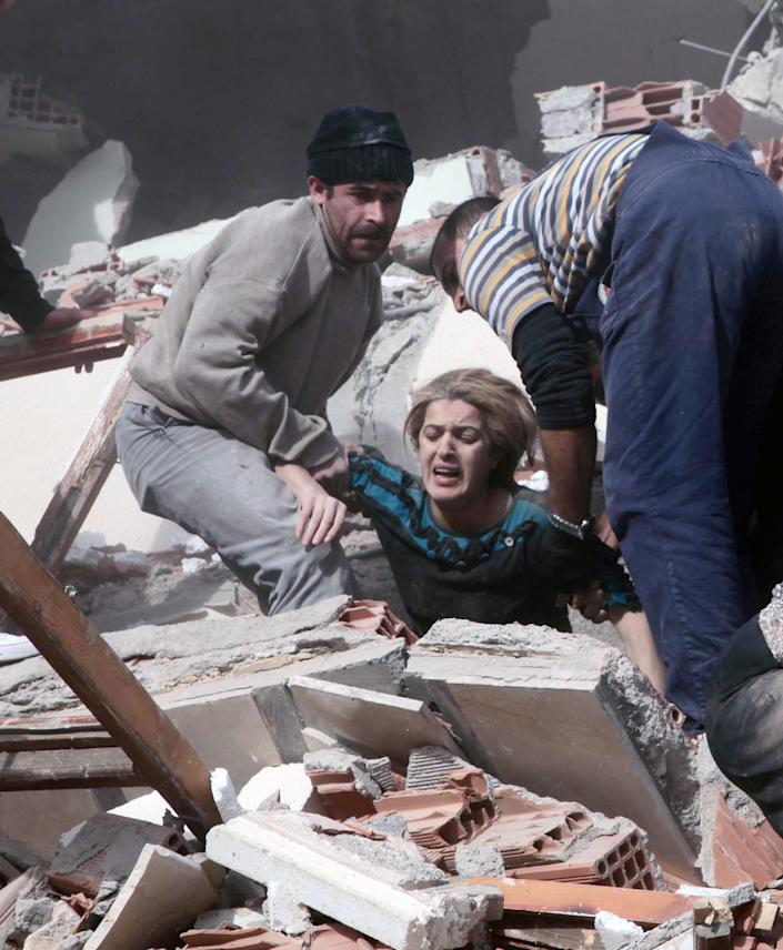 People rescue a woman trapped under debris after a powerful 7.2-magnitude earthquake struck eastern Turkey, collapsing about 45 buildings in Van province, Sunday, Oct. 23, 2011 according to the deputy Turkish prime minister. Only one death was immediately confirmed, but scientists estimated that up to 1,000 people could have been killed. The worst damage was caused to the town of Ercis, in the mountainous eastern province of Van, close to the Iranian border. ( AP Photo/ Ali Ihsan Ozturk, Aatolia)