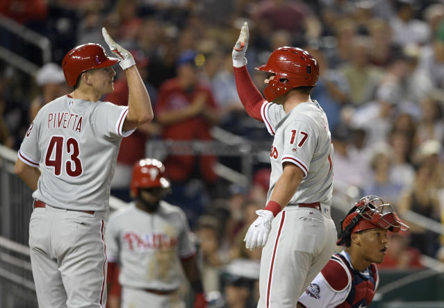 Philadelphia Phillies' Rhys Hoskins, right, celebrates his two-run home run with Nick Pivetta, left, during the third inning of a baseball game as Washington Nationals catcher Pedro Severino look on at bottom right, Sunday, June 24, 2018, in Washington. (AP Photo/Nick Wass)