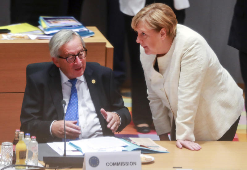 German Chancellor Angela Merkel, right, speaks with European Commission President Jean-Claude Juncker during a round table meeting at an EU summit in Brussels, Thursday, Oct. 18, 2018. EU leaders meet for a second day on Thursday to discuss migration, cybersecurity and to try and move ahead on stalled Brexit talks. (Stephanie Lecocq, Pool Photo via AP)