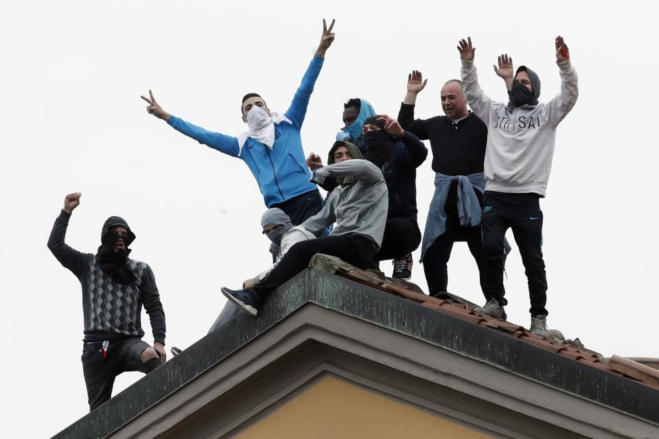 Inmates stage a protest against new rules to cope with coronavirus emergency, atop the roof of the San Vittore prison in Milan, Italy, Monday, March 9, 2020. Italy took a page from China's playbook Sunday, attempting to lock down 16 million people — more than a quarter of its population — for nearly a month to halt the relentless march of the new coronavirus across Europe. (AP Photo/Antonio Calanni)