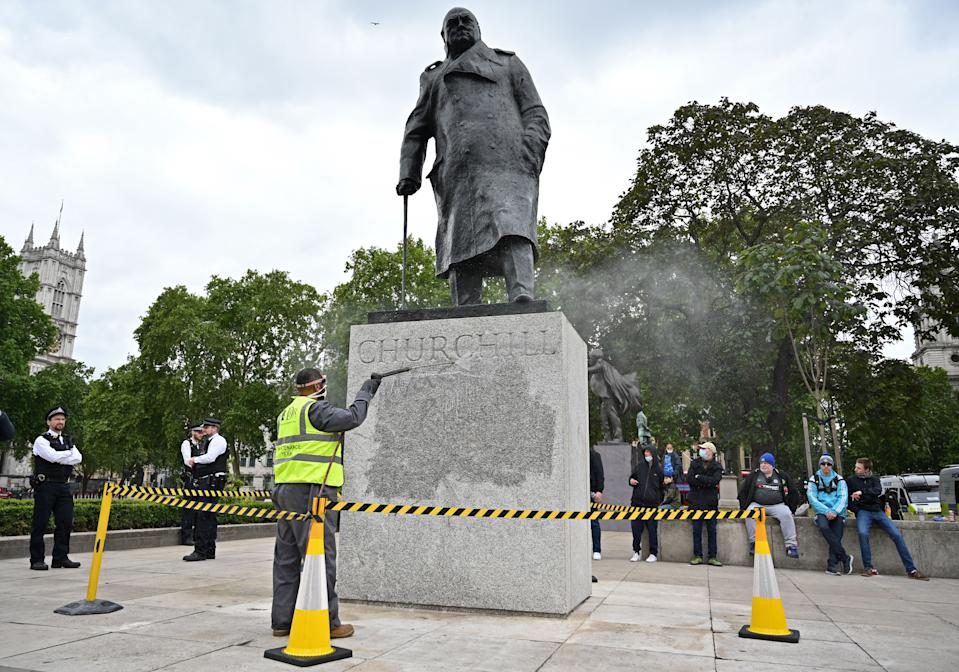 "The statue of former British prime minister Winston Churchill is cleaned in Parliament Square, central London on June 8, 2020, after being defaced, with the words (Churchill) ""was a racist"" written on it's base by protesters at a demonstration on June 7, 2020, organised to show solidarity with the Black Lives Matter movement. - Most marches at the weekend were peaceful but there were flashes of violence, including in London, where the statue of World War II leader Winston Churchill in Parliament Square was defaced. (Photo by JUSTIN TALLIS / AFP) (Photo by JUSTIN TALLIS/AFP via Getty Images)"