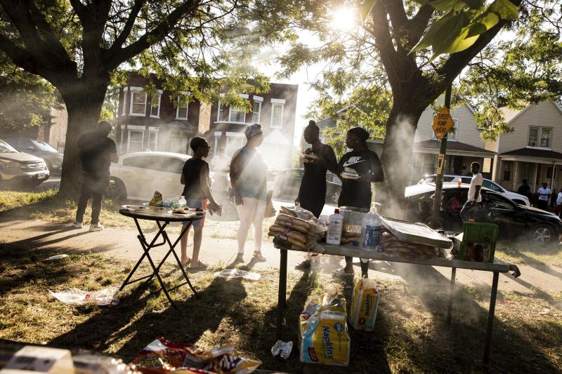 In this Thursday, Aug. 1, 2019, photo, people gather for a barbecue in a vacant lot hosted by Inner-city Muslim Action Network's (IMAN) in Chicago's neighborhood of West Englewood. IMAN seeks to educated people on proper nutrition in a section of the city with low access to nutritional foods. (AP Photo/Amr Alfiky)