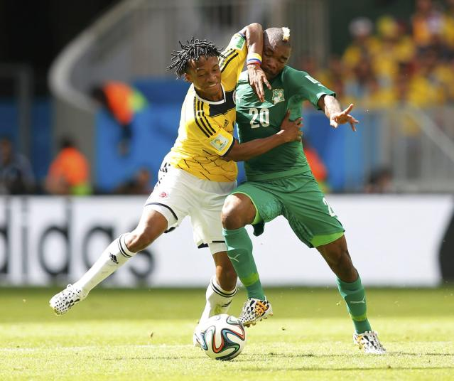 Colombia's Juan Cuadrado (L) tussles for the ball with Ivory Coast's Geoffroy Serey Die during their 2014 World Cup Group C soccer match at the Brasilia national stadium in Brasilia June 19, 2014. REUTERS/Ueslei Marcelino (BRAZIL - Tags: SOCCER SPORT WORLD CUP TPX IMAGES OF THE DAY)