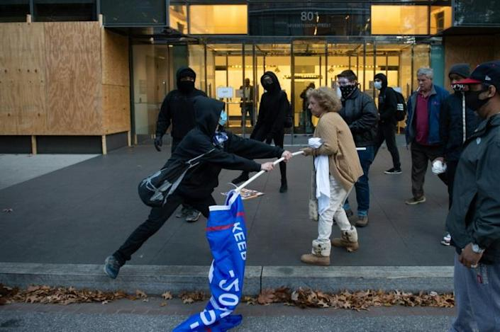 A person tries to snatch a Trump flag from a partisan following in the aftermath of the November 2020 election