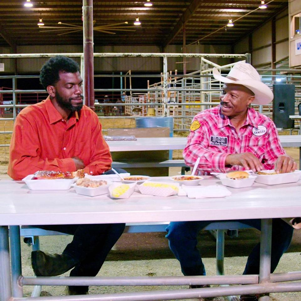 Host Stephen Satterfield (left) enjoys Texas barbecue at a rodeo with former country singer Larry Callies in the Netflix series High on the Hog, How African American Cuisine Transformed America.