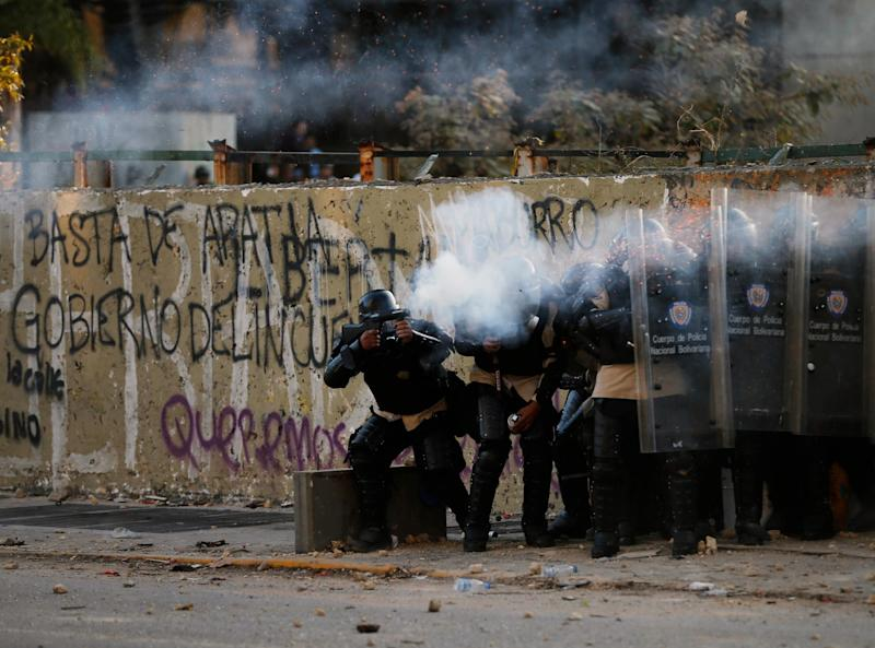 Bolivarian national police officers fire teargas at demonstrators during clashes in Caracas, Venezuela, Wednesday, March 5, 2014. The one year anniversary of the death of Venezuela's former President Hugo Chavez was marked with a mix of street protests and solemn commemorations that reflected deep divisions over the Venezuela he left behind. (AP Photo/Fernando Llano)