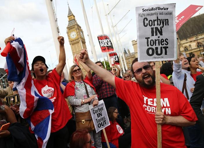 Protesters hold up signs in support of Labour Party leader Jeremy Corbyn outside parliament during a pro-Corbyn demonstration in central London on June 27, 2016 (AFP Photo/Justin Tallis)