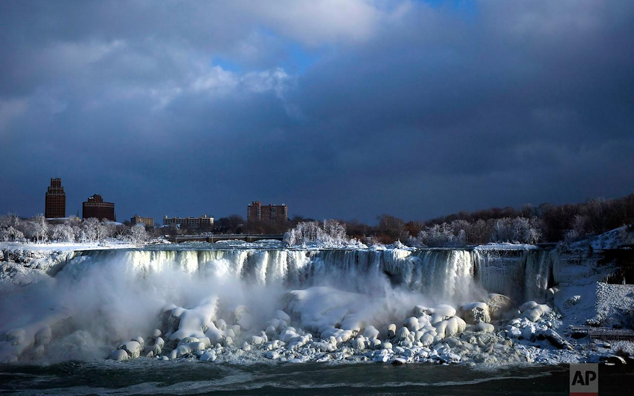 <p>Water flows over the American Falls as ice forms in this view from the Canadian side in Niagara Falls, Ontario. Almost every year frigid temperatures transform the falls into an icy winter wonderland when the mist is blown back, freezing on the landscape. (Aaron Lynett/The Canadian Press via AP) </p>