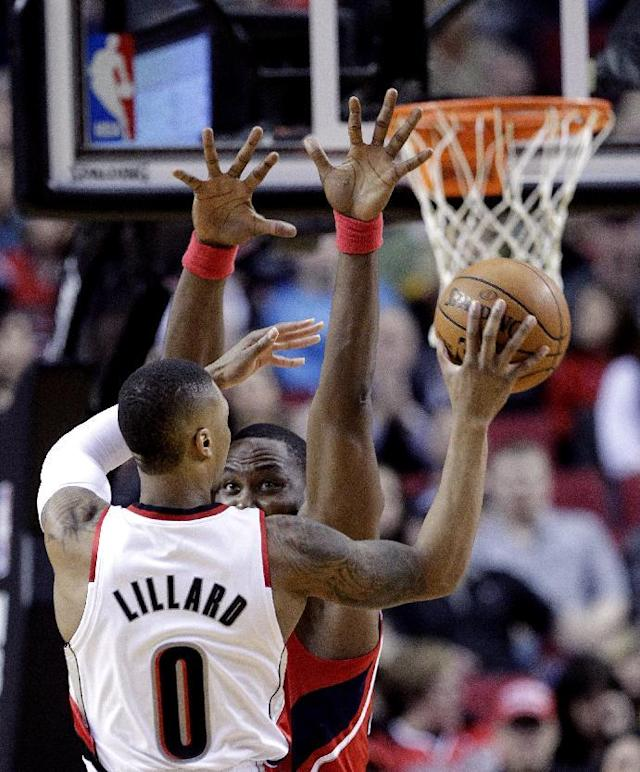 Portland Trail Blazers guard Damian Lillard, left, passes off as Atlanta Hawks center Elton Brand defends during the first half of an NBA basketball game in Portland, Ore., Wednesday, March 5, 2014. (AP Photo/Don Ryan)