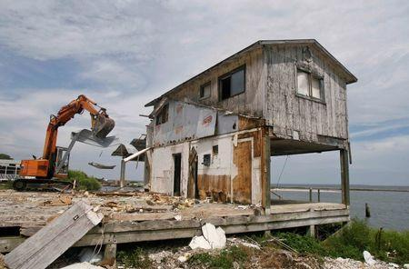 An oyster house, damaged by the storm surge of Hurricane Dennis in 2005, is demolished on the Gulf Coast in East Point, Florida, July 9, 2014. REUTERS/Phil Sears