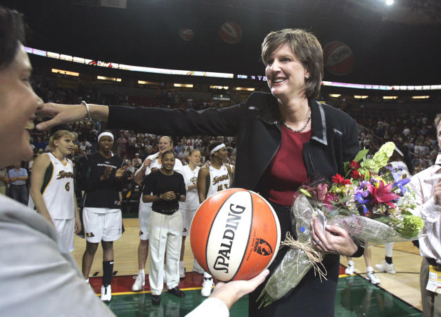 FILE - In this Aug. 19, 2005, file photo, Seattle Storm coach Anne Donovan, right, smiles as she is handed the game ball by team official Karen Bryant following the Storm's victory over the Minnesota Lyn in Seattle. The victory gave Donovan her 100th career WNBA victory as a coach, the first woman to reach that plateau. Donovan died Wednesday, June 13, 2018, of heart failure. She was 56. Donovan's family confirmed the death in a statement. (AP Photo/Elaine Thompson, File)